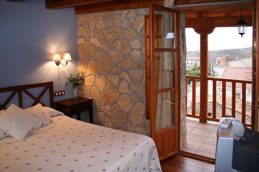 Detalle de la cama de matrimonio y el balcón